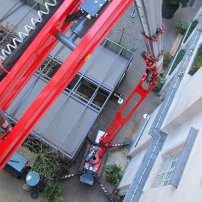 Compact uitgestempelde Hinowa spinhoogwerker tussen gebouw en fietsenstalling.