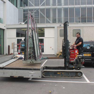 Rupsheftruck Hinowa TP1600 laadt een glasbok op een aanhangwagen.