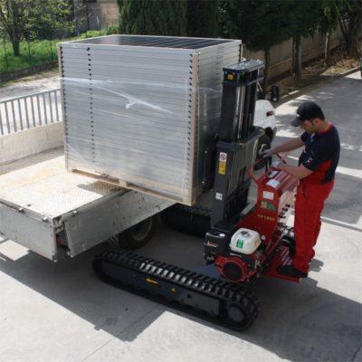 Hinowa rupsheftruck TP1800 laadt zonnepanelen in een laadbak.